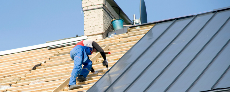 Man on roof doing maintenance after a building inspection